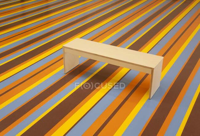 Деревянная скамейка на ярком полосатом полу — стоковое фото
