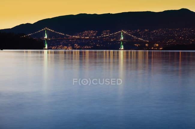 Illuminated Bridge Across a Bay and Dark Hills at Dusk — Stock Photo