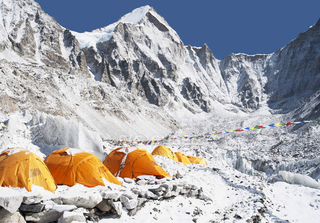 Group of orange tents at a climbers base camp in the Himalayas region. — Stock Photo