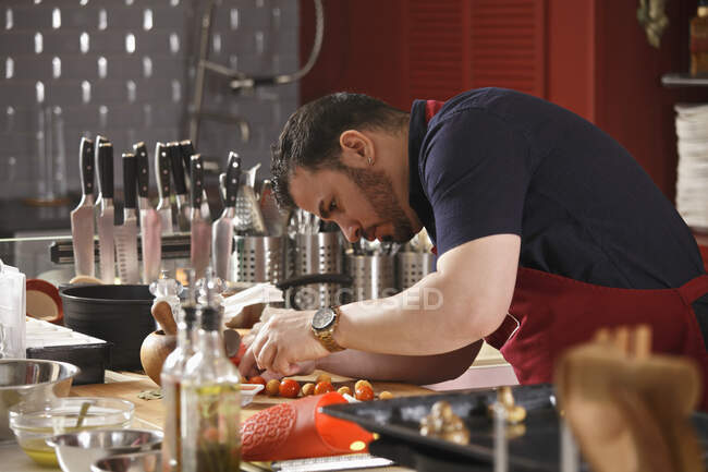 A chef bending and preparing food in a commercial kitchen — Stock Photo