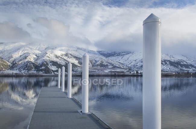 Pilares en muelle en el lago cerca de la cordillera cubierta de nieve - foto de stock