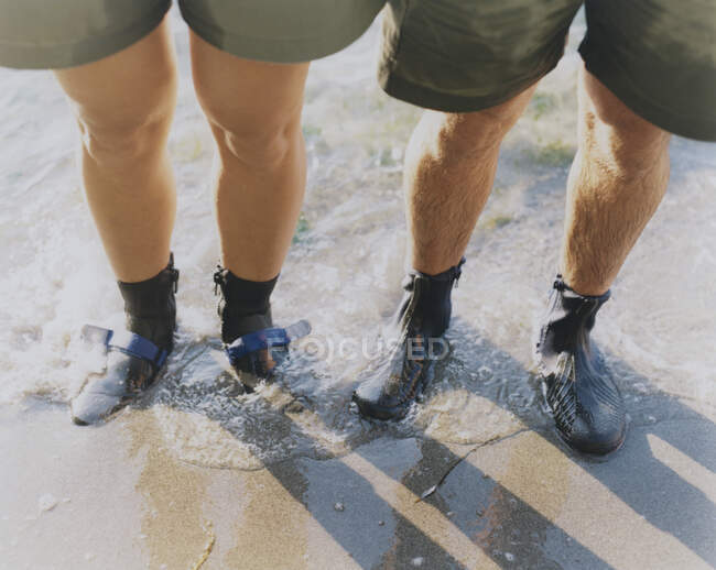 Man and woman wearing waterproof booties, standing in surf — Stock Photo