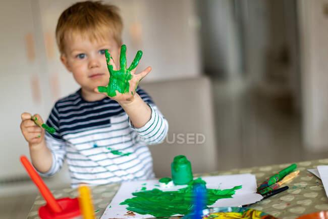 Garçon de trois ans occupé à peindre à la maison, avec des pots de peinture et des pinceaux. — Photo de stock