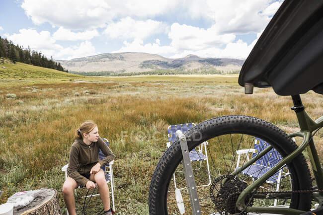 Девушка-подросток, сидящая на открытой местности и готовящаяся к велосипедной прогулке. — стоковое фото