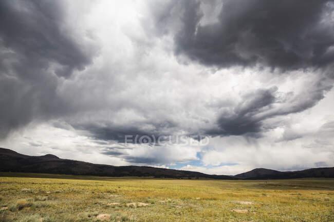 Un cielo tempestoso con pesanti nuvole grigie, montagne in lontananza. — Foto stock