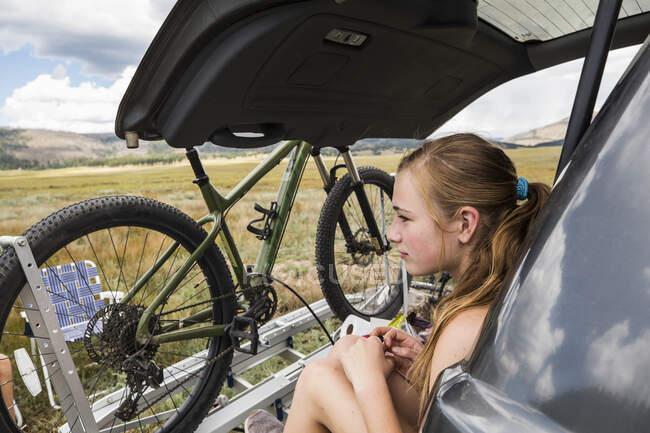 Девушка-подросток, сидящая на заднем дворе внедорожника и смотрящая на Висту — стоковое фото