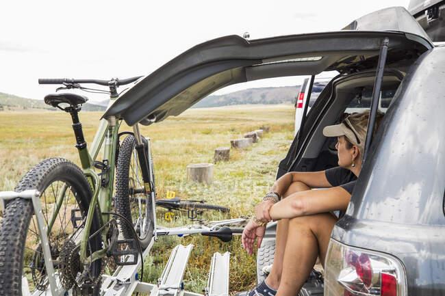 Взрослая женщина, сидящая на заднем дворе внедорожника, смотрит на Висту — стоковое фото