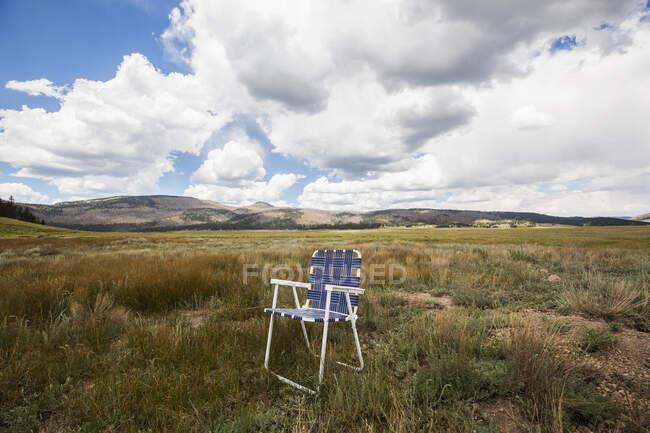 Silla plegable individual en una llanura, montañas en la distancia. - foto de stock