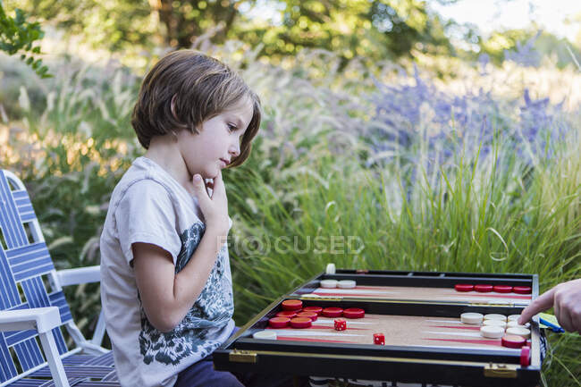 A young boy playing backgammon outdoors in a garden. — Stock Photo