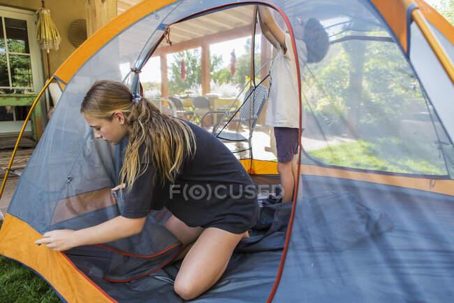 Adolescente et son jeune frère installent une tente pour dormir pendant un séjour. — Photo de stock