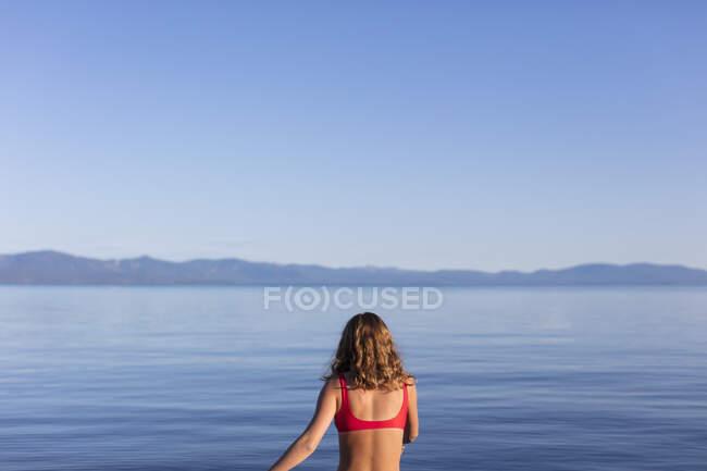 Vista desde atrás de la mujer entrando en calma, aguas azules de un lago al amanecer - foto de stock