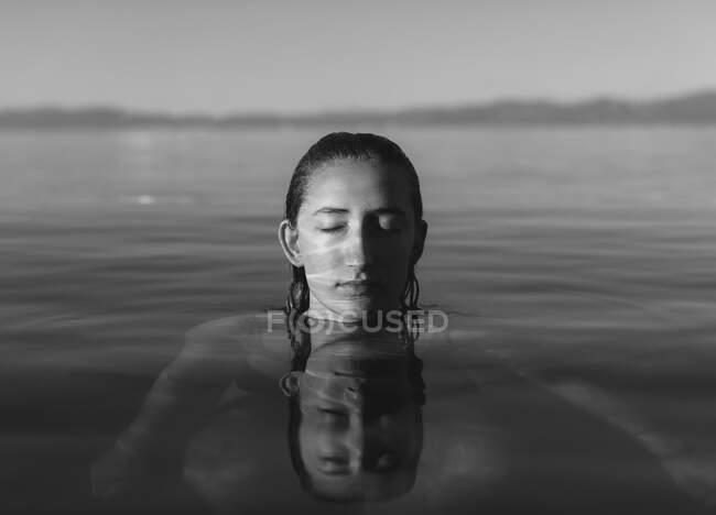 Adolescente con la cabeza por encima del agua, los ojos cerrados en el agua tranquila lago, blanco y negro - foto de stock