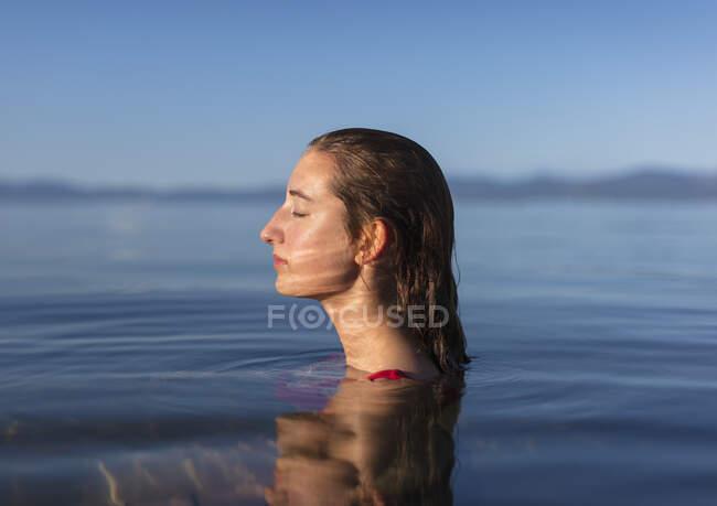 Adolescente con los ojos cerrados, cabeza y hombros por encima de las tranquilas aguas de un lago al amanecer - foto de stock