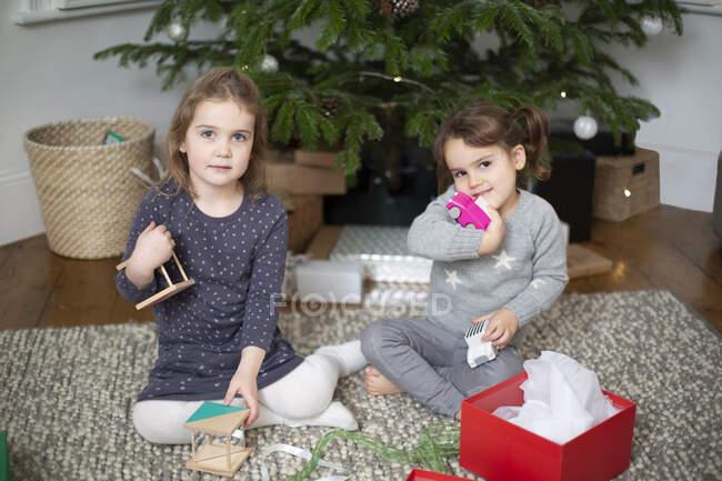 Duas meninas sentadas no chão da sala de estar, desembrulhando presente de Natal em caixa vermelha. — Fotografia de Stock