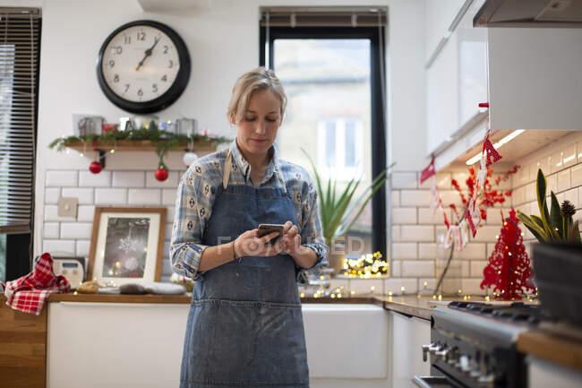 Mulher loira vestindo avental azul em pé na cozinha, usando telefone celular. — Fotografia de Stock