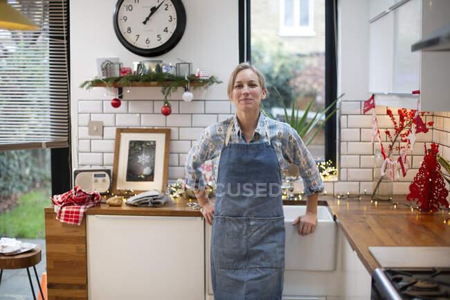 Біла жінка в синьому фартусі стоїть на кухні і посміхається перед камерою.. — стокове фото