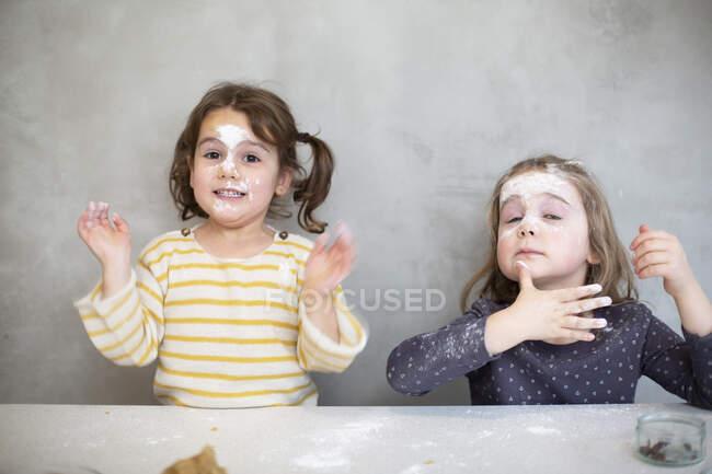 Duas meninas fazendo biscoitos de Natal, rostos cobertos de farinha e cobertura. — Fotografia de Stock