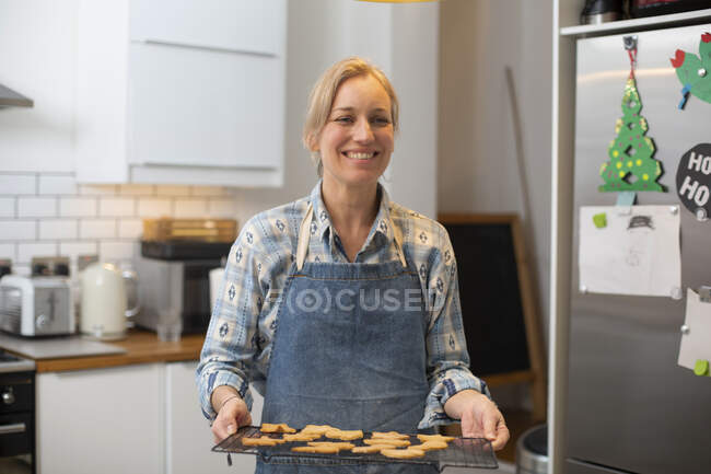 Blond woman wearing blue apron standing in kitchen, holding tray with Christmas cookies, smiling at camera. — Stock Photo