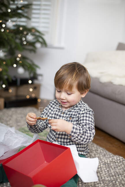 Young boy sitting on living room floor, unwrapping Christmas present in red box. — Stock Photo