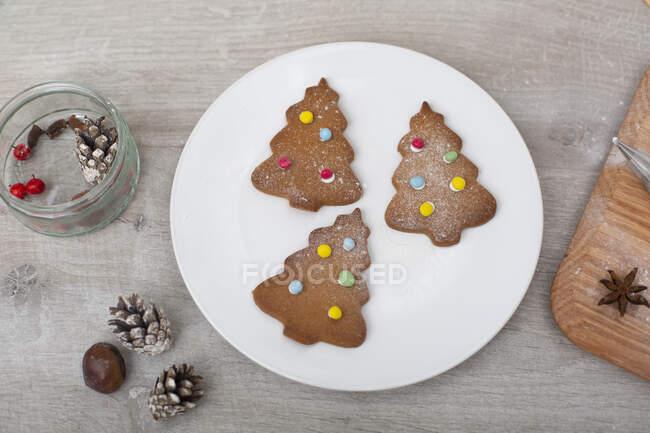 Alto angolo da vicino delle decorazioni natalizie e dei biscotti dell'albero di Natale su un piatto bianco. — Foto stock