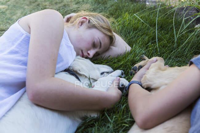Duas meninas adolescentes deitadas no gramado, abraçando seus cães Golden Retriever. — Fotografia de Stock