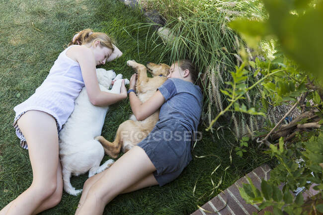 Две девочки-подростки, лежащие на лужайке, обнимают своих собак-ретриверов. — стоковое фото