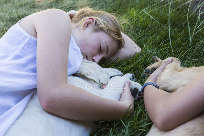 Two teenage girls lying on lawn, hugging their Golden Retriever dogs. — Stock Photo