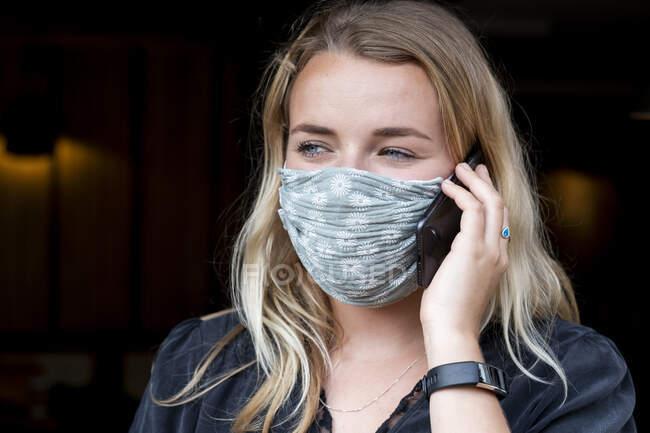 Портрет молодой блондинки в синей маске, с помощью мобильного телефона. — стоковое фото