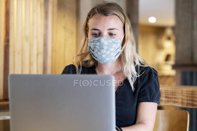 Jovem loira vestindo máscara facial azul, sentada à mesa, usando computador portátil. — Fotografia de Stock