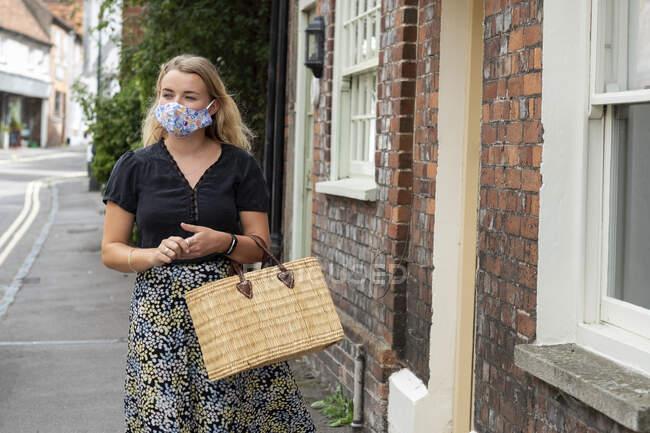 Giovane donna bionda che indossa maschera facciale passeggiando per il villaggio, portando la borsa della spesa. — Foto stock
