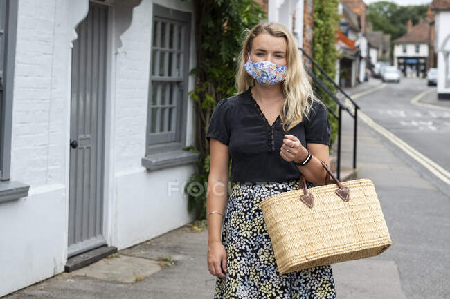 Jeune femme blonde portant un masque facial marchant à travers le village, portant un sac à provisions. — Photo de stock