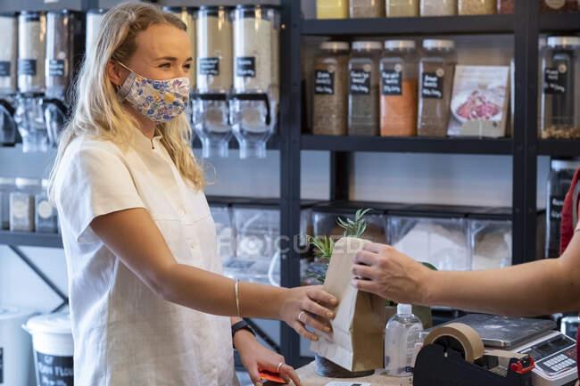 Молодая блондинка в маске для лица, делает покупки в бесплатном магазине цельной пищи. — стоковое фото