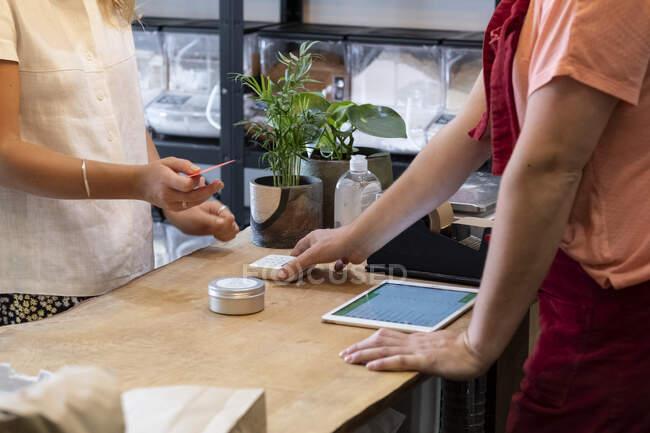 Mulher fazendo compras em loja de alimentos de todo o lixo livre, fazendo pagamento sem contato com seu cartão de crédito. — Fotografia de Stock