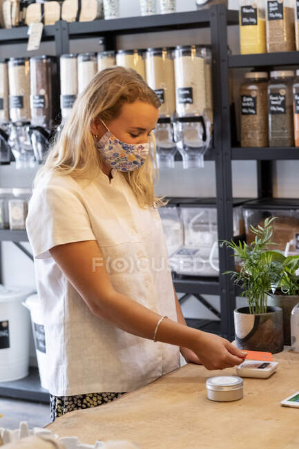 Young blond woman wearing face mask shopping in waste free wholefood store, making contactless payment with her credit card. — Stock Photo