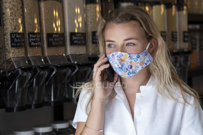 Portrait of young blond woman wearing face mask, standing in waste free wholefood store. — Stock Photo