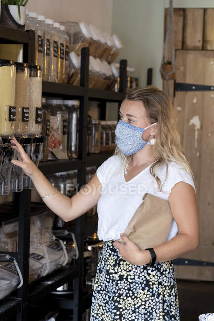 Woman wearing face mask shopping filling a paper bag with loose ingredients — Stock Photo