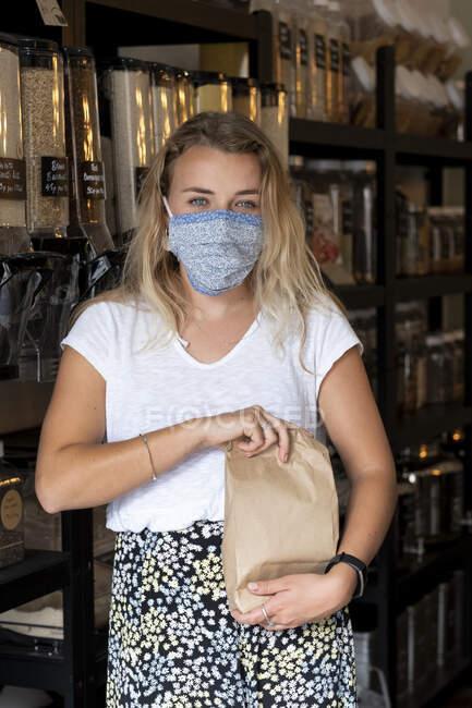 Жінка, одягнена в маску, заповнює паперовий мішок розчинними інгредієнтами. — стокове фото