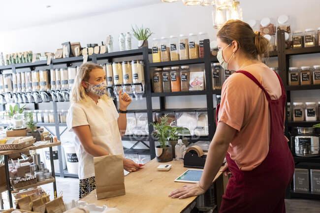 Frau mit Gesichtsmaske kauft in abfallfreiem Laden vor Ort ein, Nachhaltigkeit. — Stockfoto