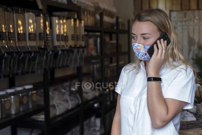 Femme portant un masque dans un magasin local sans déchets, à l'aide d'un téléphone portable — Photo de stock