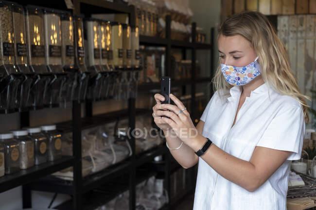 Mulher usando máscara facial em loja local sem resíduos, usando um telefone celular — Fotografia de Stock