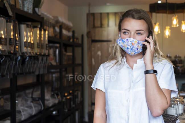 Donna che indossa maschera viso nel negozio locale senza rifiuti, utilizzando un telefono cellulare — Foto stock