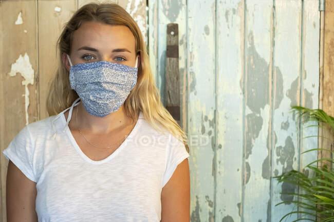 Портрет молодої блондинки, одягненої в маску обличчя, стоїть у вільному від сміття магазині.. — стокове фото