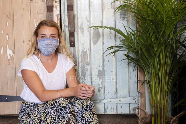 Portrait of young blond woman wearing face mask, sitting in waste free wholefood store. — Stock Photo