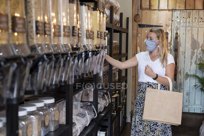 Frau mit Gesichtsmaske kauft in abfallfreiem Laden ein — Stockfoto