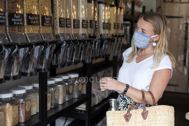 Woman wearing face mask shopping in waste-free local store — Stock Photo