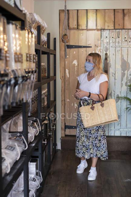 Женщина в маске для лица в магазине безотходных товаров — стоковое фото