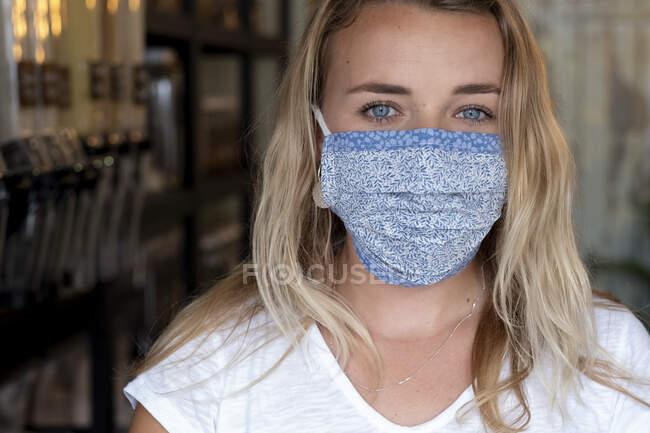 Portrait de jeune femme blonde portant un masque facial, debout dans un magasin d'aliments complets sans déchets. — Photo de stock
