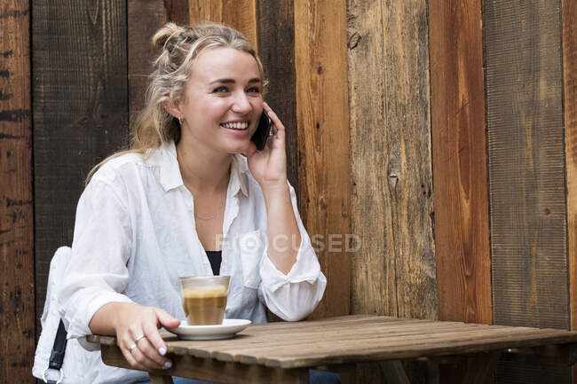 Jeune femme blonde assise seule dans un café, utilisant un téléphone portable, travaillant à distance. — Photo de stock