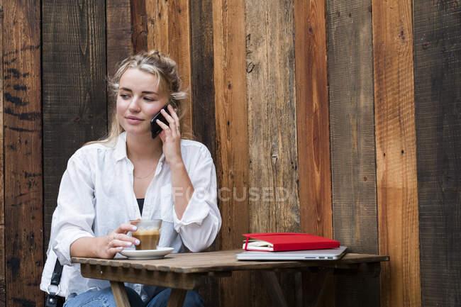 Молодая блондинка сидит одна в кафе, пользуется мобильным телефоном, работает дистанционно. — стоковое фото