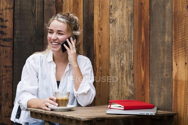 Mujer rubia joven sentada sola en un café, usando teléfono móvil, trabajando remotamente. - foto de stock